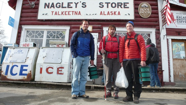 Climbers (left to right) Ian Osteyer of New York, Erik Weihenmayer of Colorado and Jay Abbie of New York get their last shopping for calories done before heading out to climb the Ham'n Eggs route on the Moose's Tooth, summit elevation 10,335 ft. Climbers, seen here toting green human waste cans, recently started trickling into Talkeetna. Photo by Diana Haecker