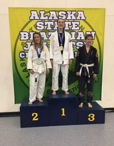 Ria Wildermuth (center) atop the podium at the Alaska State Jiu Jitsu Championship.  Photo courtesy of Pete Keenan
