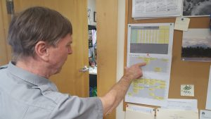 Roger Robinson looks at the schedule of arriving climbing parties.  Photo by Phillip Manning, KTNA.