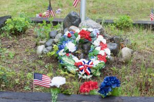 A wreath and symbols of remembrance were laid before the flag pole at the Talkeetna Cemetery on Monday.  Photo by Phillip Manning - KTNA
