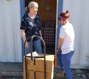 LouAnne Carroll-Tysdal [L] and volunteer Holly Beard [R] load a hand-truck to bring food into the Upper Susitna Food Pantry. Photo by Phillip Manning - KTNA