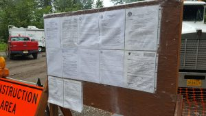 Permits fill a board near the construction site.  Photo:  Phillip Manning - KTNA